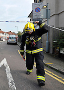© Licensed to London News Pictures. 23/09/2011. LONDON, UK. A fire officer ducks under a cordon at the scene. Six people, including three children, two teenagers and an adult have died following a house fire in Neasden, North West London today (24 Sept 2011). Emergency services were called tot he blaze in the early hours of the morning. Photo credit:  Stephen Simpson/LNP