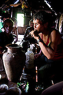 A group of Jarai ethnic men gather inside a house and drink some rice alcohol from a jar with a long straw. Pleiku area, Vietnam, Asia