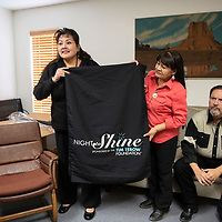 """Left to right, Verna Begay and Marietta Lynch, hold up a """"Night to Shine"""" table runner at New Life Christian Assembly of God Church, Wednesday, Jan. 9, in Pine Dale while Rev. Nathan Lynch sits next to them. """"Night to Shine,"""" is a prom night for special needs teens and adults sponsored by the Tim Tebow Foundation. New Life Christian Assembly of God Church will host a """"Night to Shine"""" event Friday, Feb. 8."""