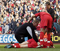 Photo. Jed Wee<br />Liverpool v Leeds United, FA Barclaycard Premiership, Anfield, Liverpool. 23/03/2003.<br />Referee Andy D'Urso (R) looks over the injured John Arne Riise after the Liverpool defender is down injured but Liverpool fail to stop playing just prior to Danny Murphy's goal.