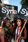 Demonstration against any intervention in Syria called by Stop the War and CND, August 30th 2013, Central London. Two young women have Syrian flags painted on their faces and hold placards saying 'Hands off Iraq'.