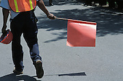 man directing traffic with orange flag