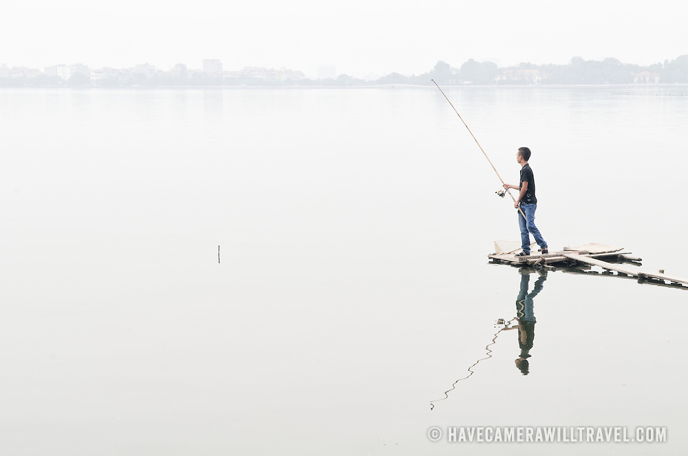 A fisherman stands on a narrow wooden jetty to cast his line from a fishing rod on West Lake (Ho Tay) in Hanoi, Vietnam. The thick haze obscures the far shore. Like most of the lakes in Hanoi, West Lake is heavily polluted, which makes the fish caught there of questionable quality for eating.