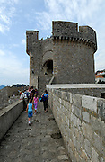 Minceta Tower and tourists walking on section of Dubrovnik old town wall, Dubrovnik, Croatia