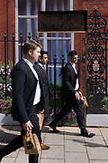 Businessmen bring back takeaway lunches, walking past the construction hoarding belonging to Claridges in Mayfair, Westminster. Having collected their takeaways from the nearby Benugos chain, they have brown bags containing their lunches and they walk in step with each other. pass the image of railings, flowers and red brickwork - all fake - printed on to the temporary hoarding.