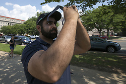 August 21, 2017 - Washington, District of Columbia, USA - SHABIB SEDDIQ of Fairfax, VA uses his eclipse glasses to take a photo of the 2017 Solar Eclipse with his iPhone. (Credit Image: © Alex Edelman via ZUMA Wire)