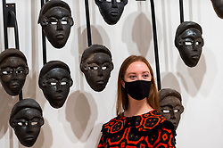 """© Licensed to London News Pictures. 27/09/2021. LONDON, UK. A staff member poses with """"Chorus"""", 2016, by Theaster Gates. Preview of """"A Clay Sermon"""", a new exhibition by Chicago artist Theaster Gates.  The display, an investigation into the significance of clay in global trade, colonial expansion, slavery and abolitionism in the UK, is on show at Whitechapel Gallery 29 September to 9 January 2022.  Photo credit: Stephen Chung/LNP"""