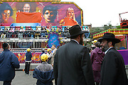 Two men watch their daughters on a fair ground ride in Springfield Park Stamford Hill to celebrate Lag B'Omer. Women and Men are kept separate at all times including children, girls and boys take it in turns to go on the rides. Lag B'Omer is the holiday celebrating the thirty-third day of the (counting of the) Omer. Jews celebrate it as the day when the plague that killed 24,000 people ended in the holy land (according to the Babylonian Talmud). Other sources say the plague was actually the Roman occupation and the 24,000 people died in the second Jewish - Roman war  (Bar Kokhba revolt of the first century).  Bonfires (used as signals in wartime) are symbolically lit to commemorate the holiday of Lag'B'Omer.