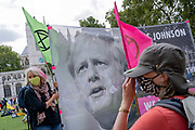 After a postponed break because of the Coronavirus pandemic,  Climate Change activists protest with a banner featuring the image of Prime Minister Boris Johnson in Parliament Square, on 2nd September 2020, in London, England.