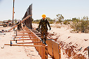 12 JUNE 2006 - SAN LUIS, AZ: A Utah Army National Guard soldier walks on concrete forms used for the construction of a fence on the US/Mexico border. Fifty five members of the 116th Engineer Company, Combat Support Engineers, of the Utah Army National Guard are in San Luis, AZ, to build a fence and improve roads east of the San Luis Port of Entry on the US/Mexico border. The unit is the first of an estimated 6,000 US military personnel, almost all of them Army National Guard, who will be dispatched to the US/Mexico border by President Bush to help control immigration on the border. The Guardsmen will primarily build roads and fence and staff surveillance centers. They will not be engaged in first line law enforcement work.  Photo by Jack Kurtz