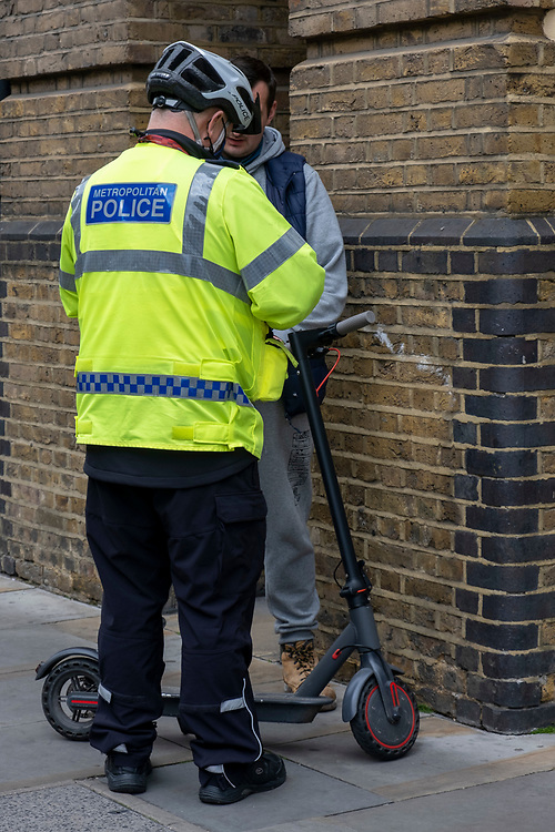 A metropolitan police officer takes down the details of a male E-scooter rider that he stopped riding on the pavement on Tooley Street, SE1 on the 25th of May 2021 in London, United Kingdom. (photo by Andrew Aitchison / In pictures via Getty Images)
