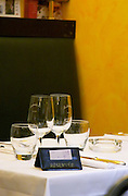 A restaurant table with a sign saying Reserve Réservé showing that the table is reserved booked. White linen table cloth, wine glasses. At the restaurant Le Gourmandin. in Beaune Cote d'Or Burgundy Bourgogne France Europe