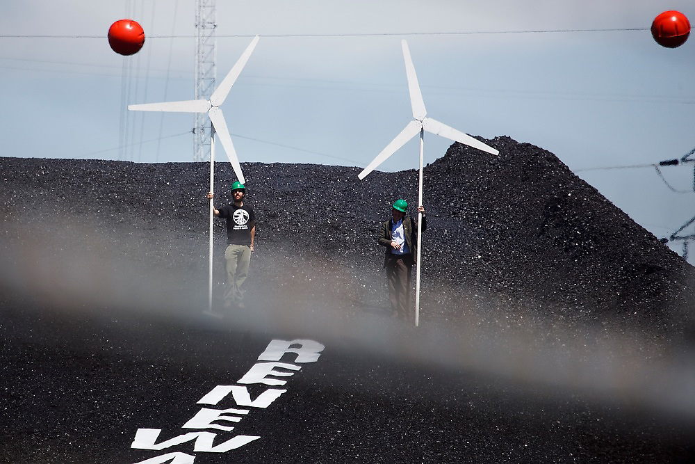 Eric Ross (l-r) and Tom Weiss stand proudly with mock wind turbines on top of the large coal mound at the Valmont Power Plant in Boulder, Colorado on April 27, 2010. During the protest for more renewables, Ross, Weiss and two other climate activists claimed the coal mound for over an hour before being arrested for trespass.