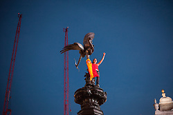 © licensed to London News Pictures. London, UK 01/07/2012. A Spanish football fan climbs to the Eros Statue in Piccadilly Circus, London, as their team win the Euro 2012 final in Kiev. Photo credit: Tolga Akmen/LNP