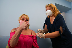 © Licensed to London News Pictures. 05/06/2021. London, UK. Sunbritt Poulsen gestures as Covid-19 vaccinator, Julie Rose-Wood administers the AstraZeneca vaccine to her at a vaccination centre in Haringey, north London. The UK will offer first doses of the COVID-19 vaccine to people over the age of 25 from next week. Photo credit: Dinendra Haria/LNP