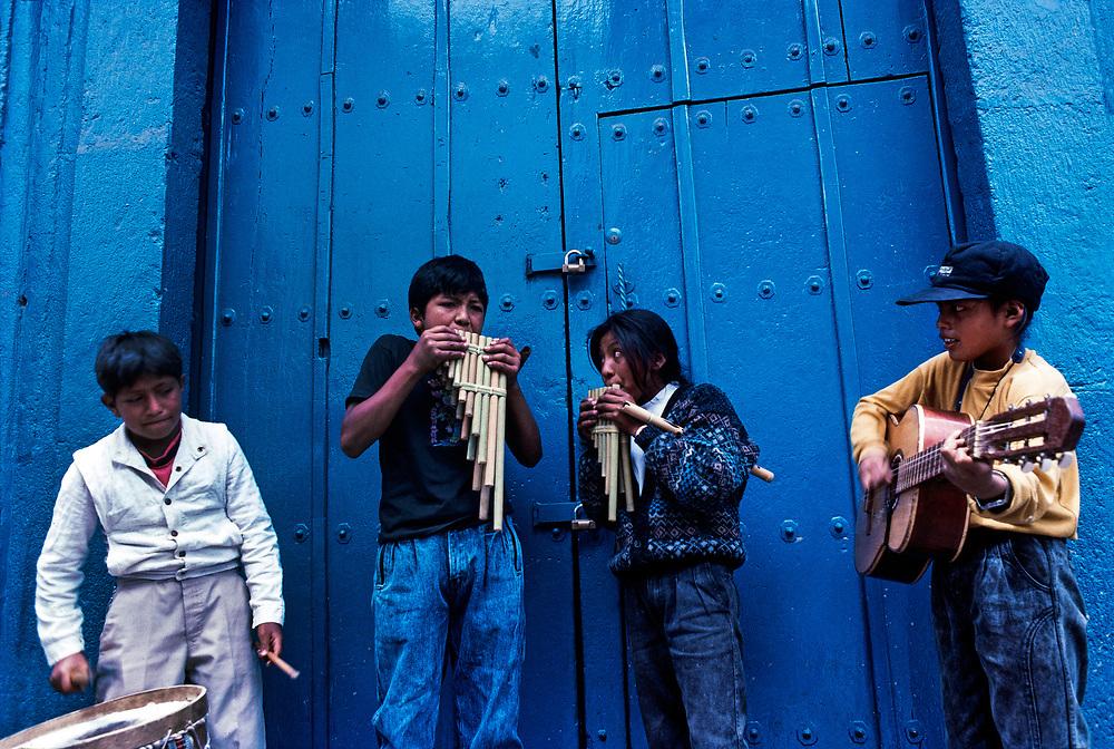 Otavaleno boys busking outside church at the Saturday weekend market, Otavalo, Ecuador