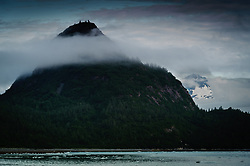 """""""The Nunatak"""" rises out of low clouds near Nunatak Cove in Glacier Bay National Park and Preserve in southeast Alaska. The Nunatak is a 1,205 foot glaciated knob located on the east side of the Muir Inlet."""