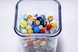 glass marbles in a clear plastic rectangular storage container