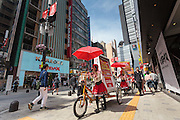 Japanese women wheel bicycles with advertising on them  under a model of Godzilla  on the new Toho Shinjuku building in Kabukicho, Shinjuku, Tokyo, Japan. Friday April 24th 2015.