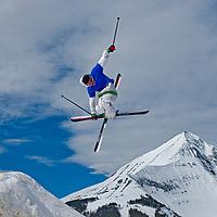 SKIING. Ben Wiltsie (MR) skis aerial manouvers off jump in terrain park at Big Sky Ski Resort, near Bozeman, Montana. 11,166-foot Lone Mountain  bkg.