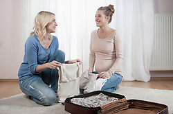 Packing suitcase pregnant woman girlfriend helping