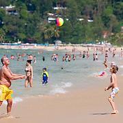 Father and son play ball on Karon beach in Phuket, Thailand