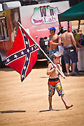 Young boy walks with a confederate flag during the annual Summer Redneck Games Dublin, GA.