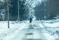 A man takes a motorcycle for a ride on a snow covered street in a small rural community in central Illinois.
