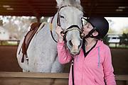 Mature women kissing a horse