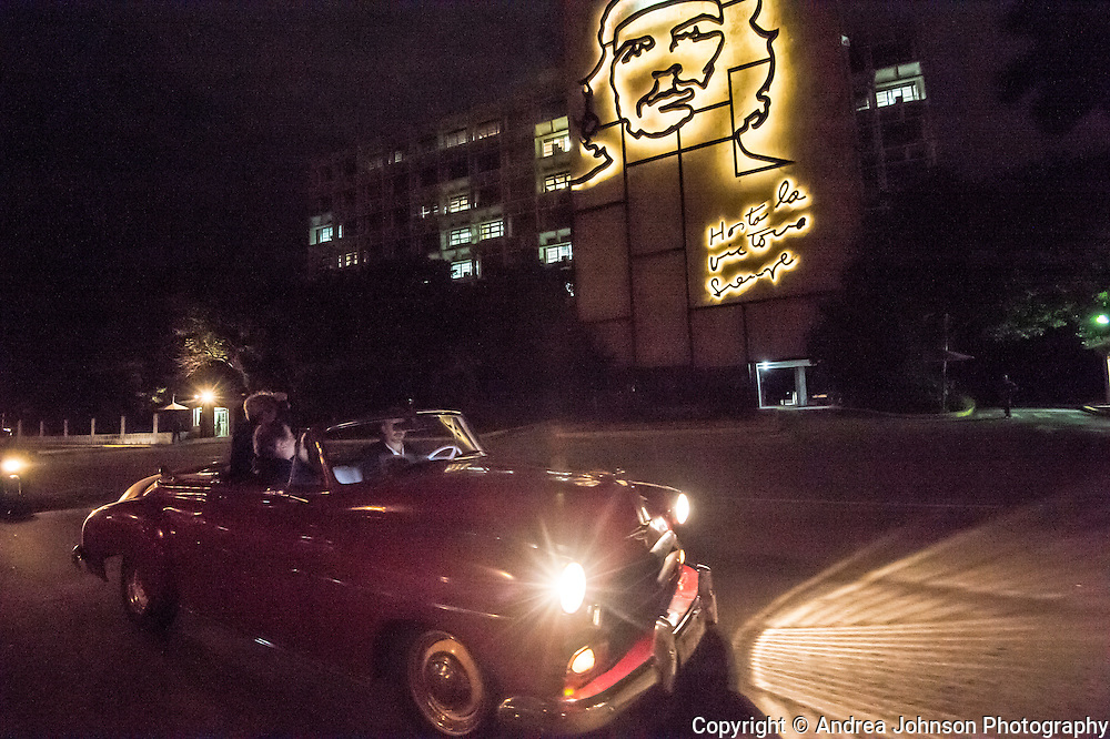"Touring in classic cars past  revolutionalry image of  Che Guevara with the words ""Hasta la Victoria, Siempre"" (Until Victory, Always).at Plaza de la Revolucion (""Revolution Square"" ), Havana"