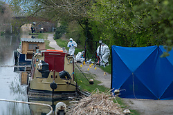 © Licensed to London News Pictures. 27/04/2021. Aylesbury, UK. Forensic investigators gather evidence at the scene following a fatal assault near Bridge 14 on the Grand Union Canal near Broughton in Aylesbury at about 12.20pm on Monday 26/04/2021. Police officers found a man with serious injuries and despite the efforts of emergency services the man died at the scene. Photo credit: Peter Manning/LNP