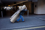 A workman manhandles a heavy roll of carpet in a Mayfair street, central London.