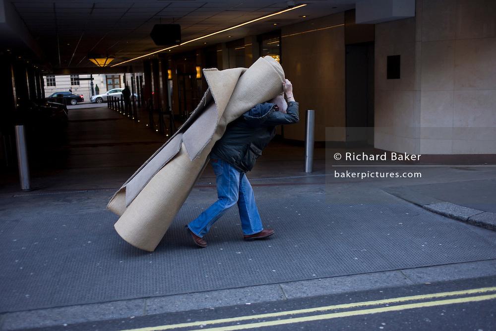 A workman manhandles a heavy roll of carpet in a Mayfair street, central London.