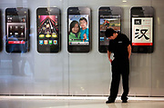 A security guard stand in front of advertisements for Apple Inc's iPhone 4 at the opening of the company's new store in Shanghai, China, on Friday, Sept. 23, 2011. Apple Inc. is currently has 5 stores in mainland China as it struggles to open enough stores to stave off competition of its popular iPhones and iPads