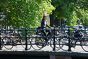 Young woman cycling on bridge across Brouwersgracht in Amsterdam, Holland