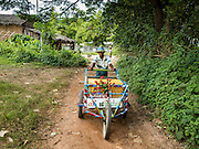 30 OCTOBER 2015 - TWANTE, MYANMAR: A snack vendor pushes his cart in the potters' village in Twante, (also spelled Twantay) Myanmar. Twante, about 20 miles from Yangon, is best known for its traditional pottery. The pottery makers are struggling to keep workers in their sheds though. As Myanmar opens up to outside investments and its economy expands, young people are moving to Yangon to take jobs in the better paying tourist industry or in the factories that are springing up around Yangon.     PHOTO BY JACK KURTZ