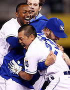 Kansas City Royals' Norichika Aoki (23) is congratulated by Jarrod Dyson, top left, Aaron Crow, top, and Danny Duffy, right, after hitting in the game-winning run in the 14th inning of a baseball game against the Cleveland Indians at Kauffman Stadium in Kansas City, Mo., Thursday, July 24, 2014.  (AP Photo/Colin E. Braley)