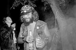 Late Night Around the Campfire. Sturgis, SD. 1979<br /> <br /> Limited Edition Print from an edition of 50. Photo ©1979 Michael Lichter.<br /> <br /> Description: Late at night by the campfire, a bottle passed. Time and the world beyond just a concept. A chance to share stories and tails of the road. One by one, drifting off, only a few remain. Voices interrupt the quiet. Silence as dawn breaks.