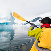 A kayaker paddles through calm waters past an iceberg at Cuverville Island on the Antarctic Peninsula.