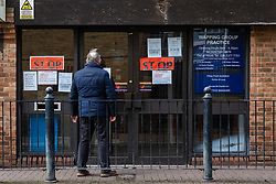 © Licensed to London News Pictures. 15/03/2020. London, UK. A man looks at 'STOP' signs on the door of Wapping Health Centre in east London. Wapping Health Centre has announced that from Monday 16th March, all new appointments at the GP surgery will be made by telephone triage only, to minimise cross infection and protect their medical workforce from coronavirus and has stated that any patients with pre-booked appointments next week should not come into the surgery but instead wait for a telephone call from their doctor. Photo credit: Vickie Flores/LNP