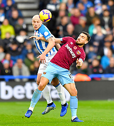Huddersfield Town's Aaron Mooy (left) and West Ham United's Robert Snodgrass battle for the ball during the Premier League match at the John Smith's Stadium, Huddersfield.