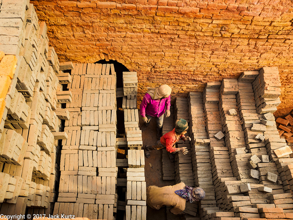 09 MARCH 2017 - BAGMATI, NEPAL: Workers stack unbaked bricks in a kiln at a brick factory in Bagmati, near Bhaktapur. There are almost 50 brick factories in the valley near Bagmati. The brick makers are very busy making bricks for the reconstruction of Kathmandu, Bhaktapur and other cities in the Kathmandu valley that were badly damaged by the 2015 Nepal Earthquake. The brick factories have been in the Bagmati area for centuries because the local clay is a popular raw material for the bricks. Most of the workers in the brick factories are migrant workers from southern Nepal.           PHOTO BY JACK KURTZ