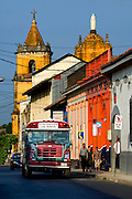 Early morning street scene shows local bus and people going to work in Leon, Nicaragua.  The Iglesia de la Recoleccion rises above the street in the background.