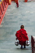 Young monk carrying a pots of tea for morning ceremony at Thiksey Monastery, Ladakh, India