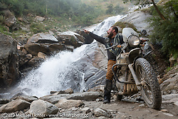 Motorcycle Sherpa's Bear Haughton on his Royal Enfield Himalayan at a roadside waterfall on the Ride to the Heavens motorcycle adventure in the Himalayas of Nepal. On the fifth day of riding, we went from Muktinath to Tatopani. Friday, November 8, 2019. Photography ©2019 Michael Lichter.