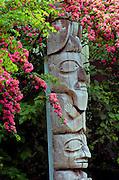 Alaska, Juneau ,Tlingit native totem pole with flowers outside the State Museum.