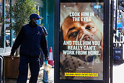 """© Licensed to London News Pictures. 29/01/2021. London, UK. A man wearing a protective face covering turns round  to look at the government's 'Look him in the eyes - And tell him you really can't work from home.' publicity campaign poster in north London. Covid-19 infection rates are continuing to drop across London. But health experts are warning Londoners to follow the lockdown rules, as """"any relaxation would risk a rapid reversal or decline."""" Photo credit: Dinendra Haria/LNP"""