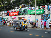 29 SEPTEMBER 2016 - BANGKOK, THAILAND: A tuk-tuk (three wheeled taxi) goes past supporters of the residents of Pom Mahakan lining the city wall in front of the old fort. Forty-four families still live in the Pom Mahakan Fort community. The status of the remaining families is not clear. Bangkok officials are still trying to move them out of the fort and community leaders are barricading themselves in the fort. The residents of the historic fort are joined almost every day by community activists from around Bangkok who support their efforts to stay.     PHOTO BY JACK KURTZ