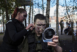 © licensed to London News Pictures. London, UK 13/10/2012. A man puts on zombie make-up in Southbank, London as more than 2,000 'zombies' celebrating World Zombie Day on 13/10/12 in London. Photo credit: Tolga Akmen/LNP