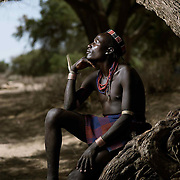 Bola Gooda sits casually under a tree on the banks of a dry river bed.<br />